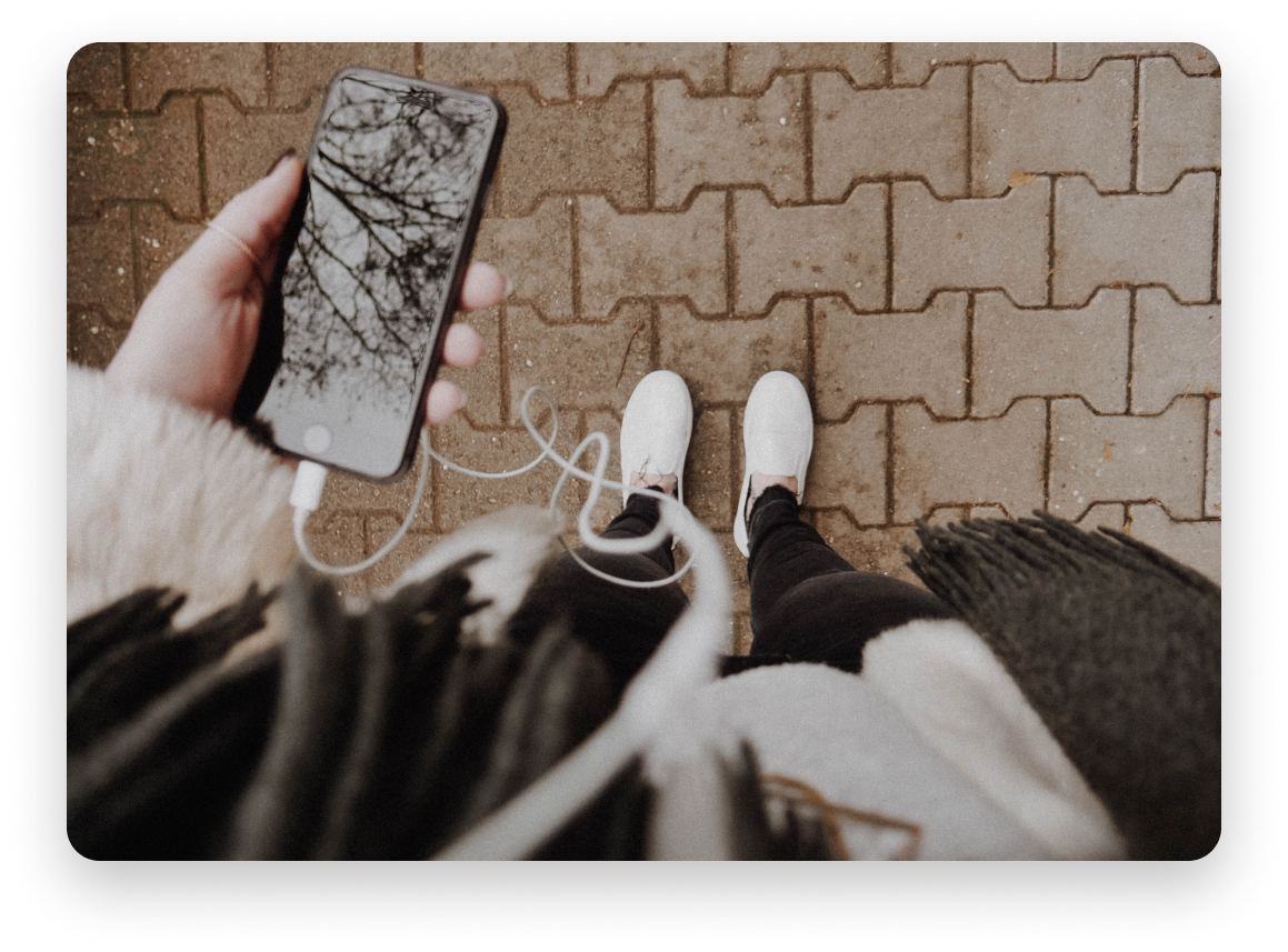 Staring down at a phone and white shoes standing on brick sidewalk