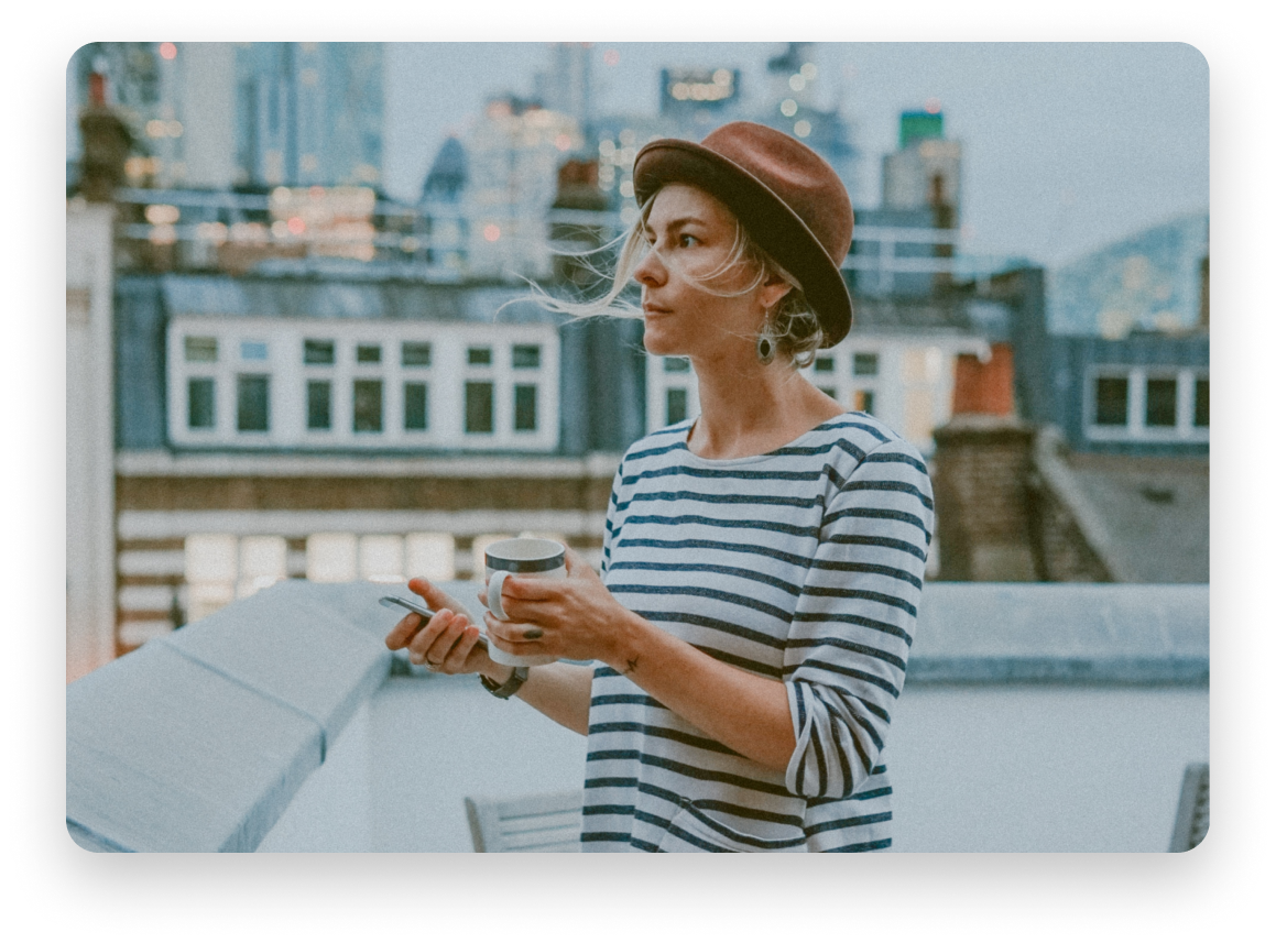 Woman with brown hat and stripped shirt on a rooftop holding a mug and a cell phone