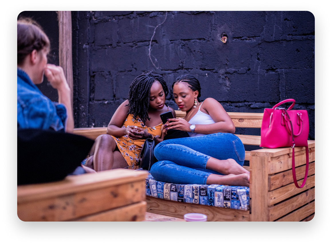 Two women looking at phone while sitting on a bench