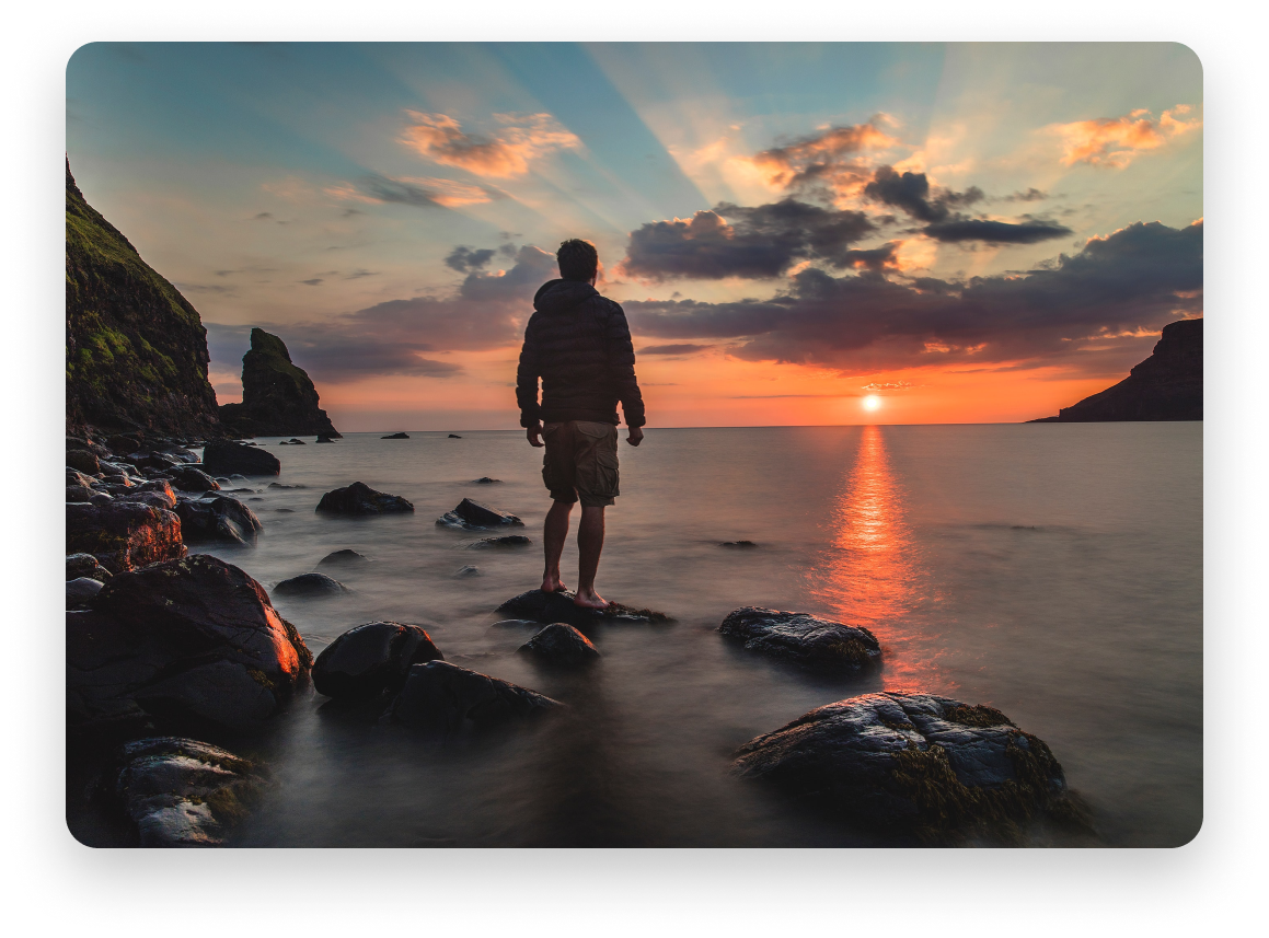 Man standing on rocks in calm water looking out at a stunning sunset.