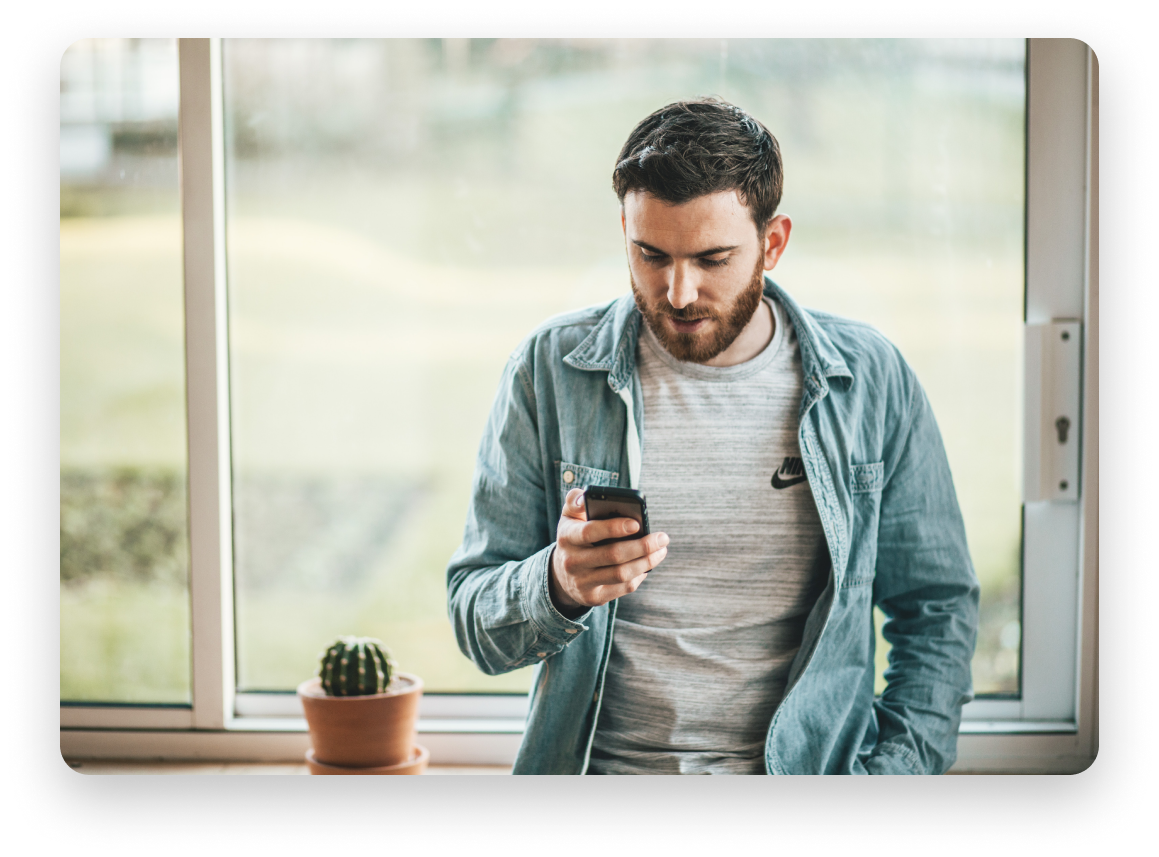 Man in jean shirt in front of a window texting on his phone.