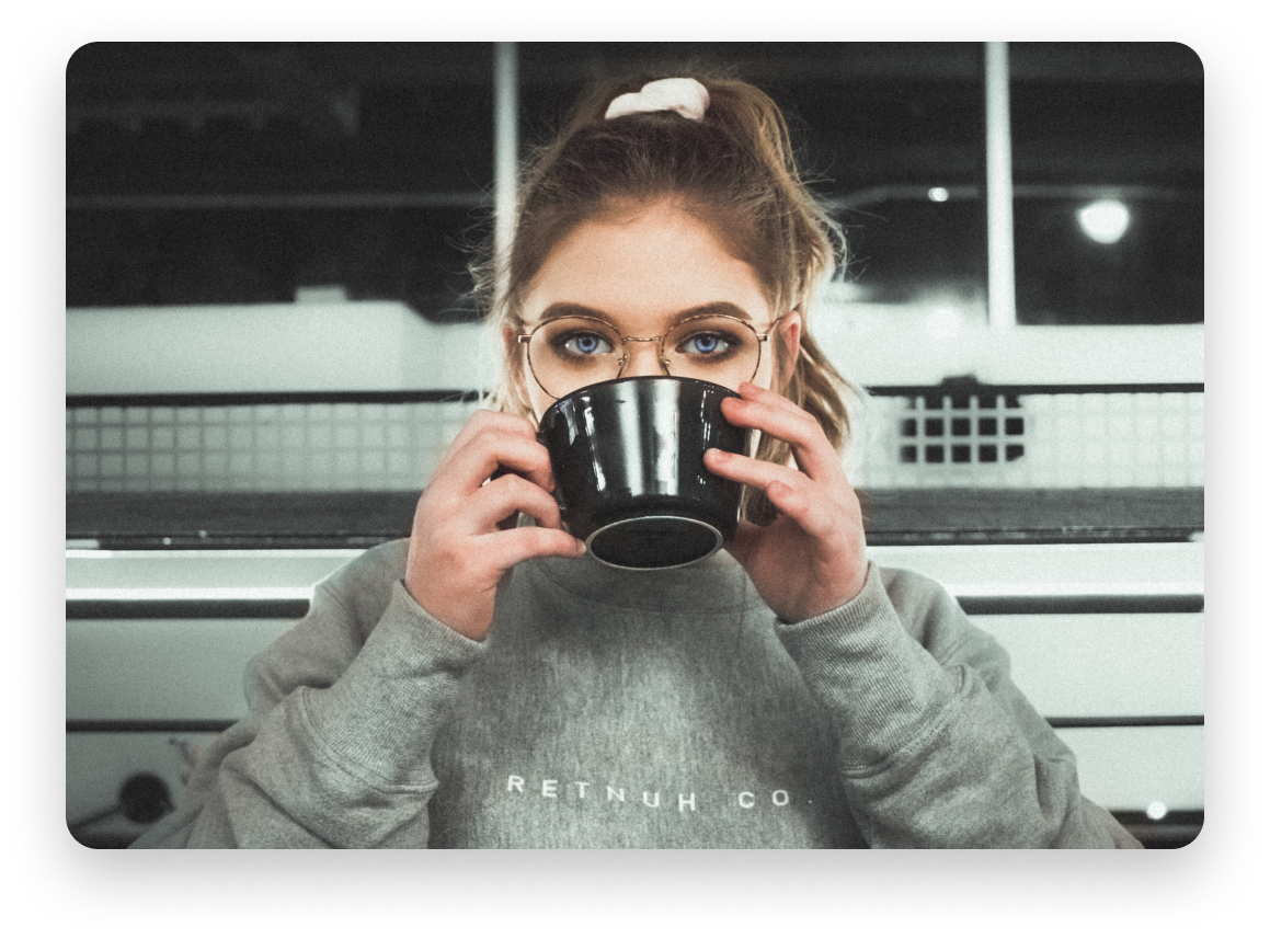 Woman with a ponytail and piercing blue eyes drinking from a coffee mug