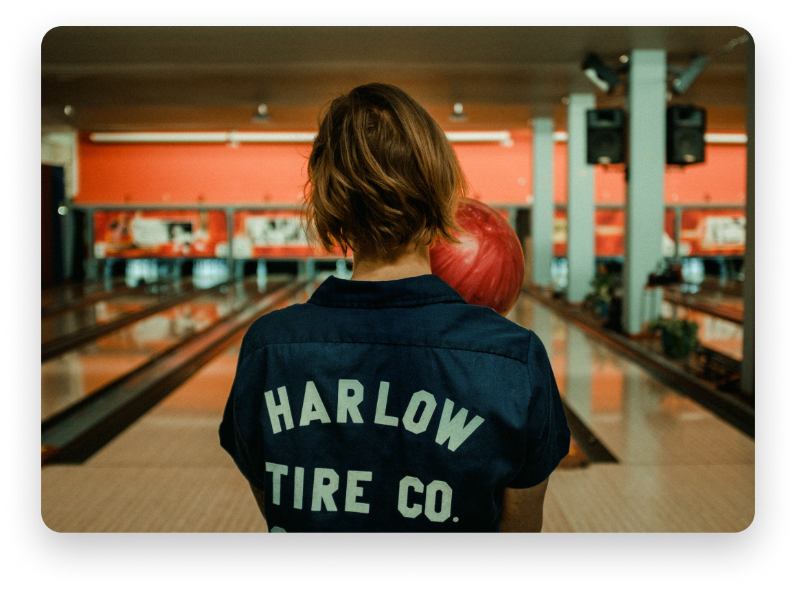 Photo of a woman's back as she bowls, holding a bowling ball.