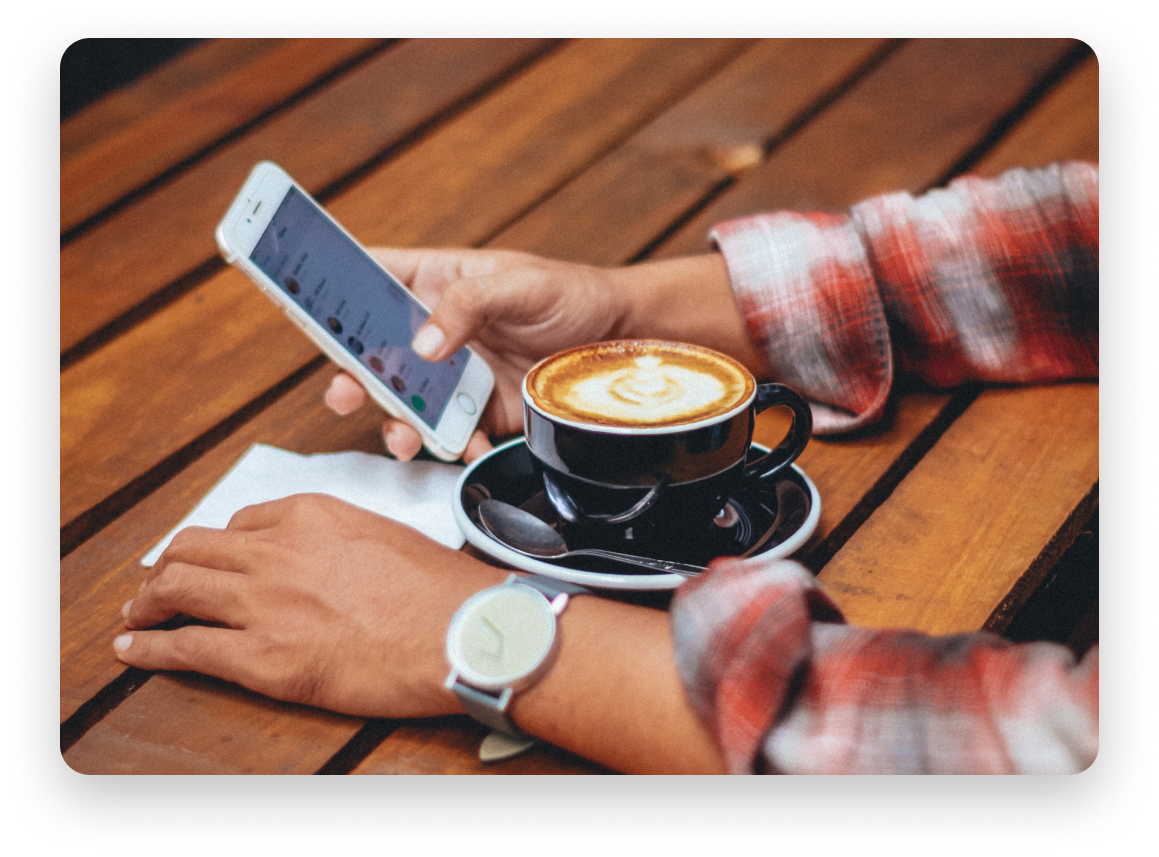 Woman on her phone with a latte in front of her