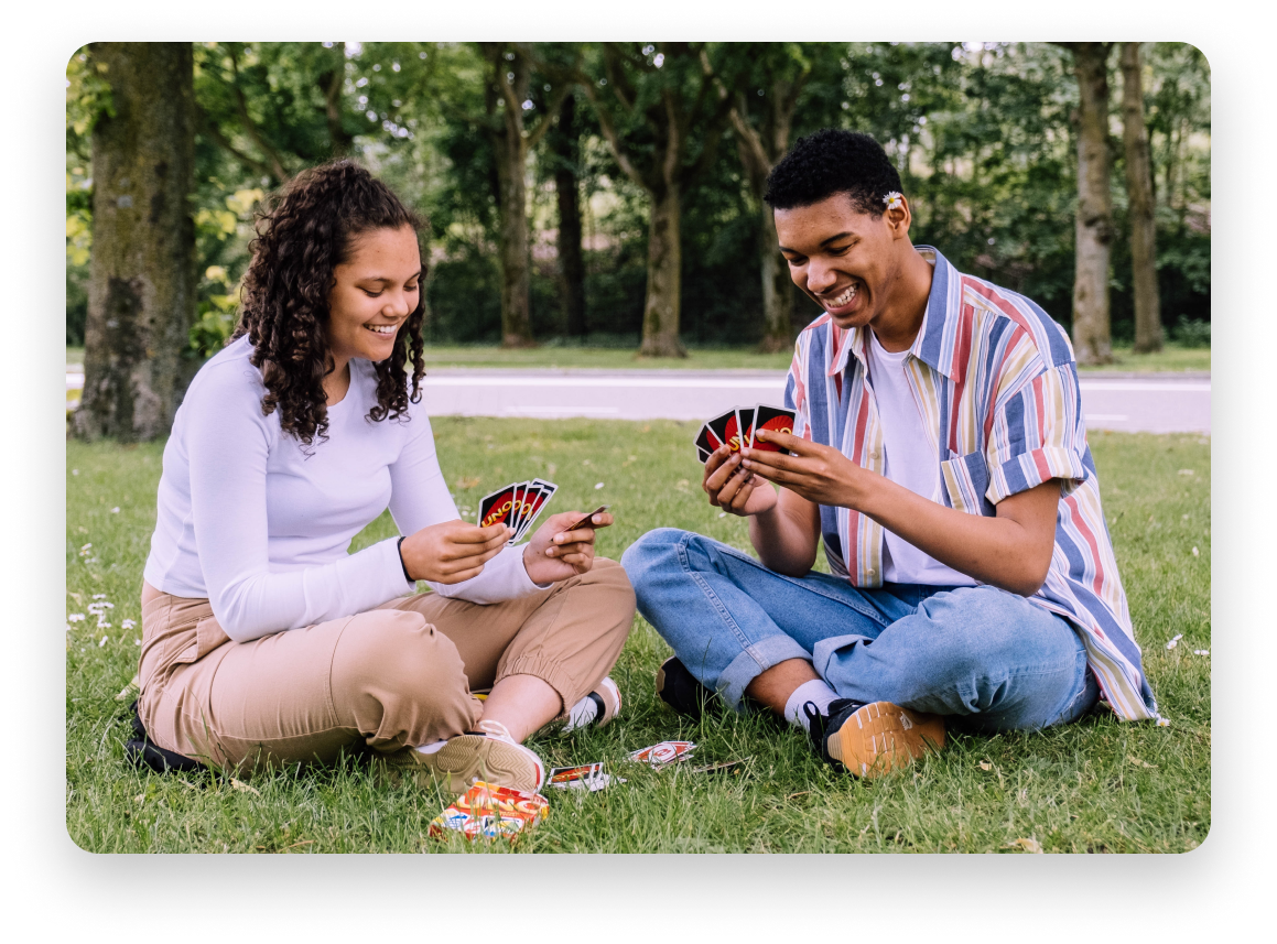 Man and woman playing cards in a park