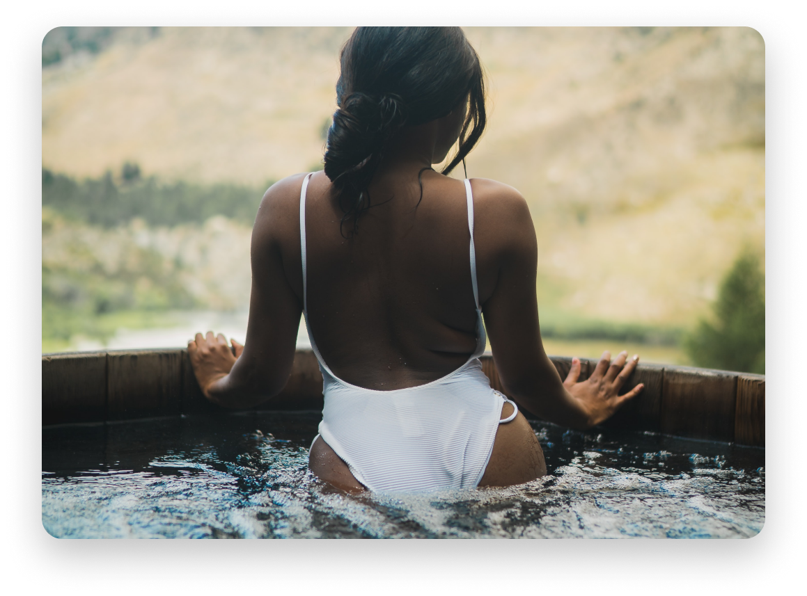 Woman in a white bathing suit, photo of her back, facing natural scenery