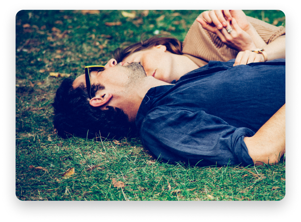 Engaged couple laying on the grass, man wearing a blue shirt and sunglasses, woman wearing beige cardigan