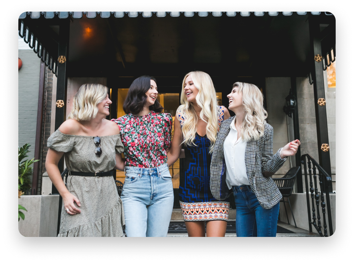 4 fashionable dressed friends laughing with arms linked, three blonde one brunette