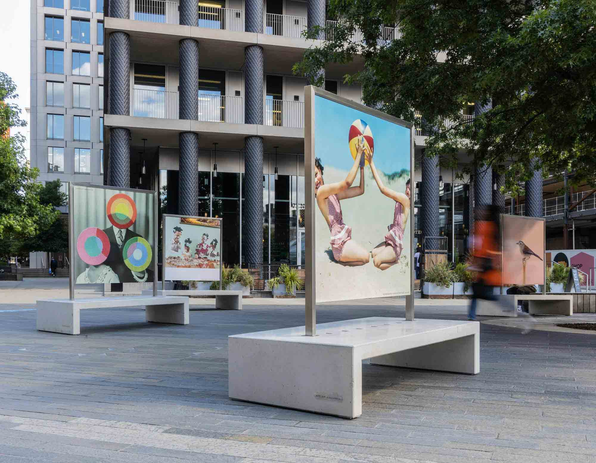An installation in King's Cross, London, UK., of specially-made benches with canvas overhead, displaying images from The Photographer's Gallery