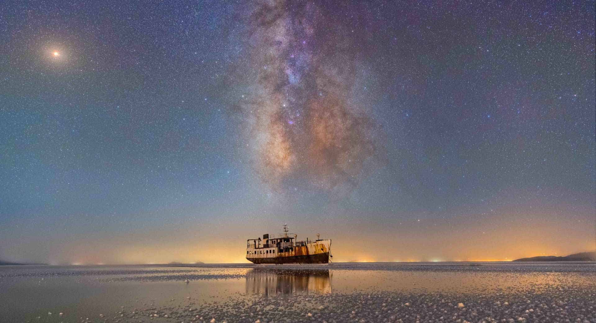 A boat in the middle of an arctic ocean, surrounded by a star-filled blue and purple sky