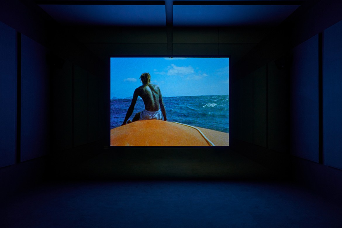 A projected film by Steve McQueen in a dark lit and blue room
