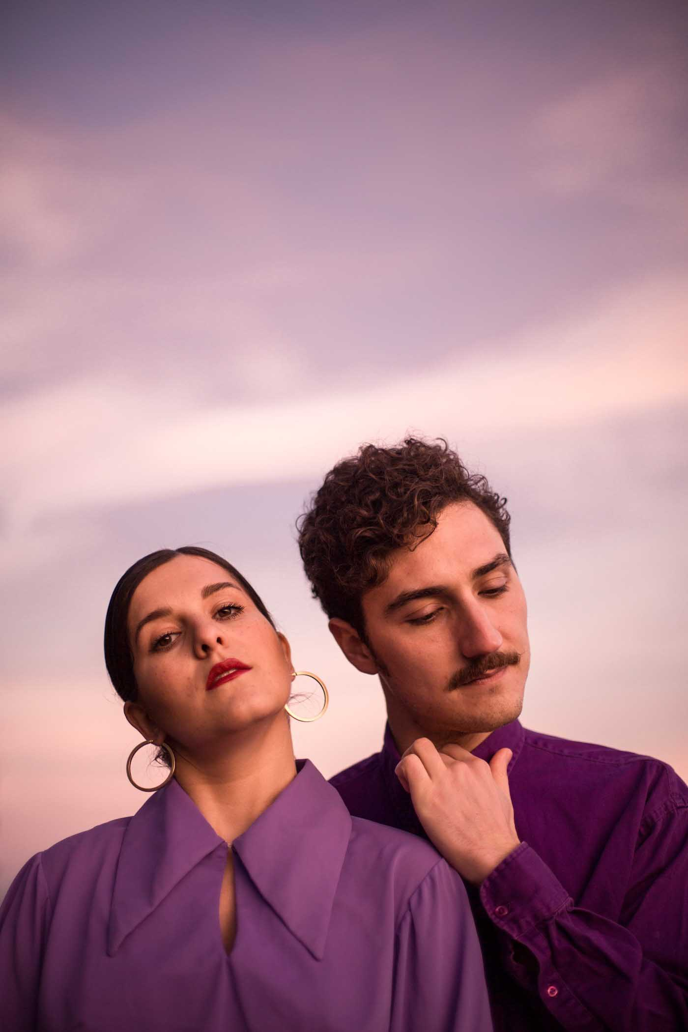 Close-up portrait of singer and guitarist duo, M w S, wearing purple shirts, against a pink and orange sky at sunrise at Hampstead Heath, London, UK.