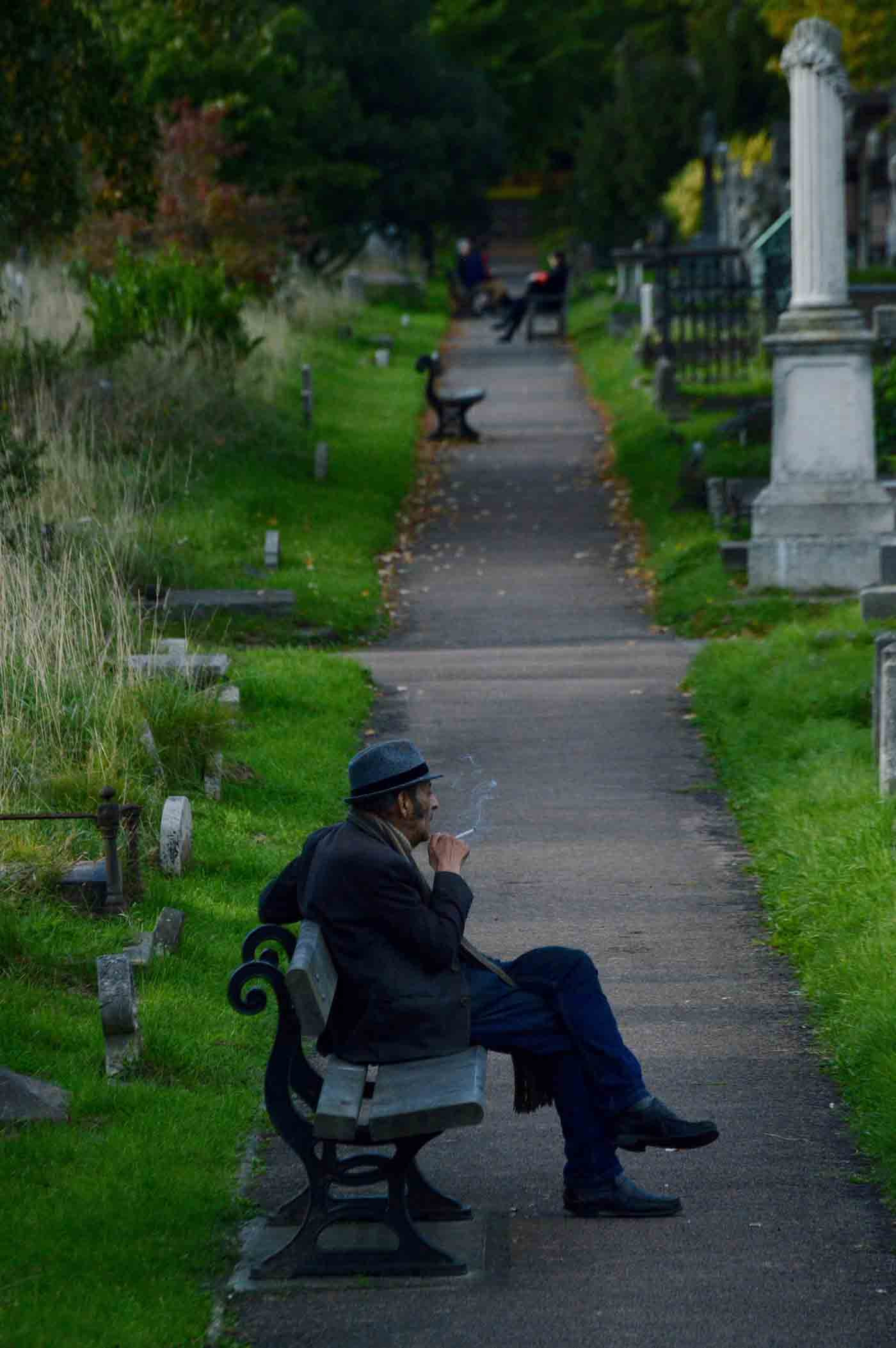 Man smoking a cigarette and sitting on bench on a path at Brompton Cemetery, Fulham, London.