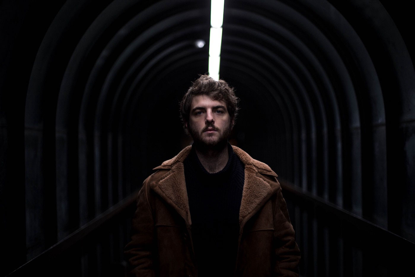 Portrait of a filmmaker and photographer, Jon Victor Lara, in a corridor with one neon strip light above his head, at the Barbican Centre, London, UK.