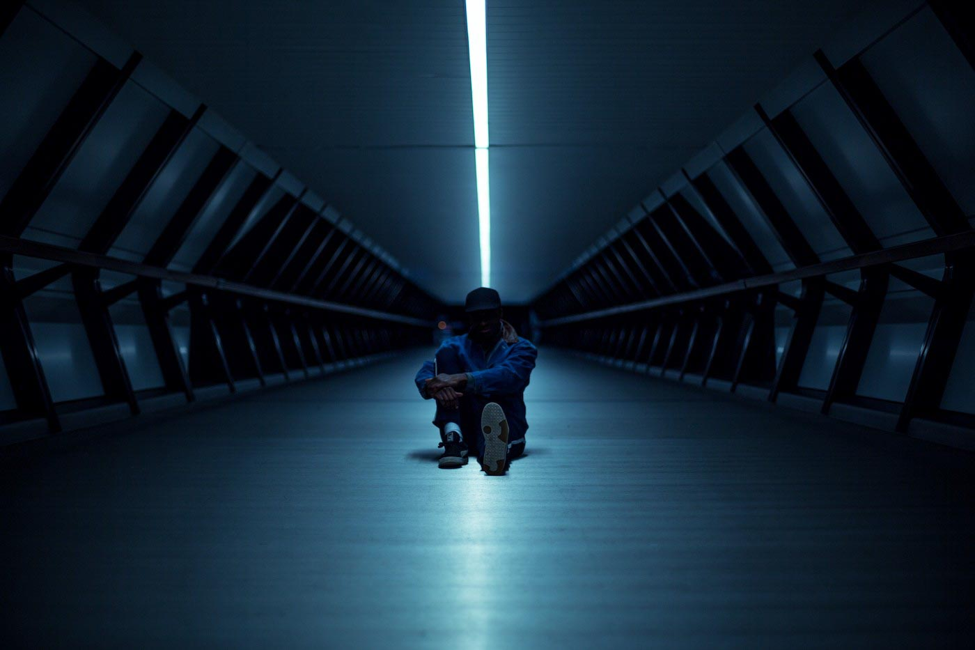 Silhouette of rapper, Timo, sitting in a dark corridor, lit by one continuous white neon light down the hall, at Adam's Place, Canary Wharf, London