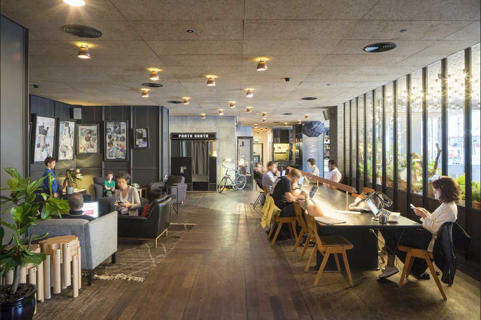 Interior of Ace Hotel's cafe, with people sitting on couches and at tables working, in East London