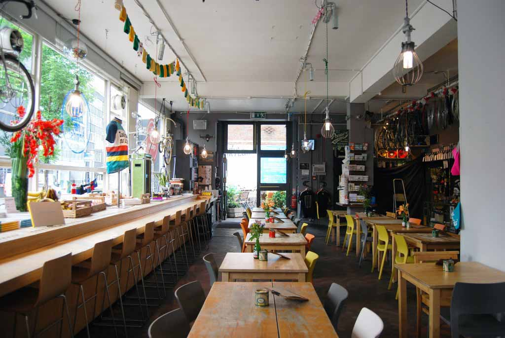 Interior of coffee shop and bike shop, Look Mum No Hands, with wooden tables in the space, in East London