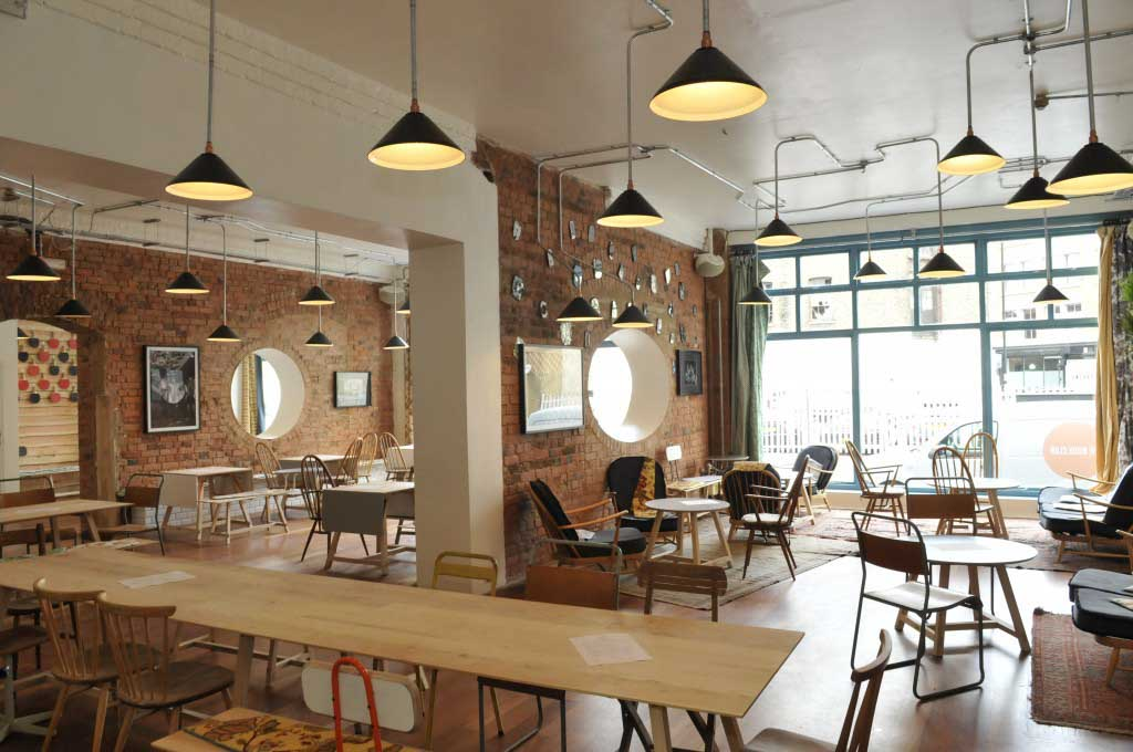 Interior of coffee shop, The Book Club, with wooden chairs and tables throughout the space, in East London