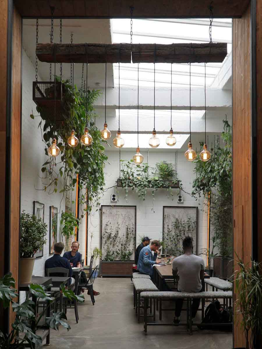 Interior of coffee shop, Hackney Coffee Company, with a large common wooden table in the centre of the space and people working, in East London