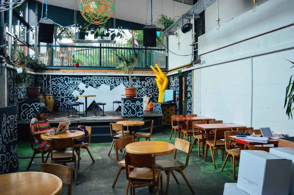 Interior of restaurant and even space, Grow, with wooden tables on a grassy floor and a woman working in the corner, in Hackney Wick, East London