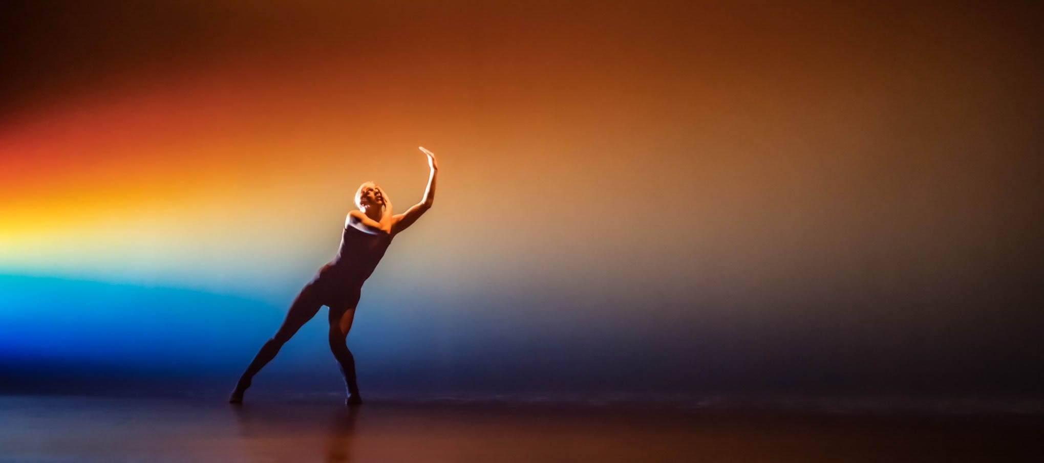 Woman dancing at Sadler's Wells, London, backlit with orange and blue lights