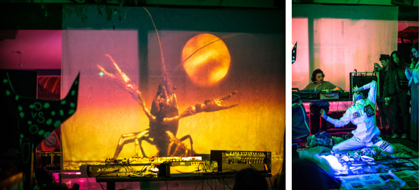 Orange and yellow projection of a lobster next to an image of a performance, featuring a man dressed in white, on the floor