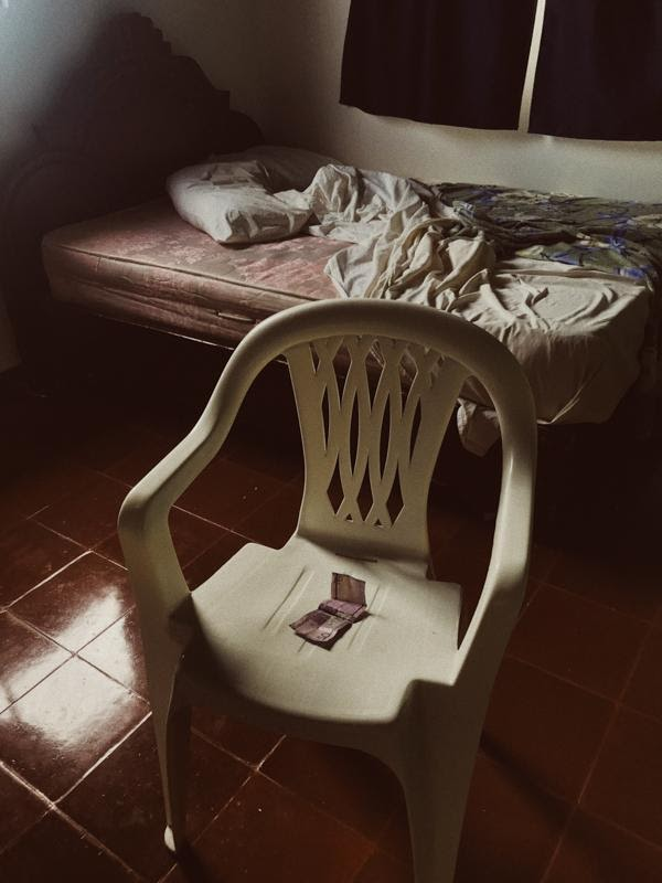 Pesos on a white plastic chair in the middle of a hotel room in the Dominican Republic, with an unmade bed in the background