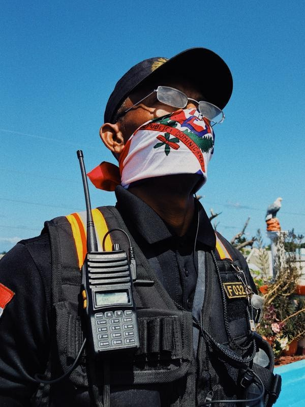 A member of a private police in the Dominican Republic, wearing a scarf for a mask, with a walk talkie hanging onto his protective upper body equipment