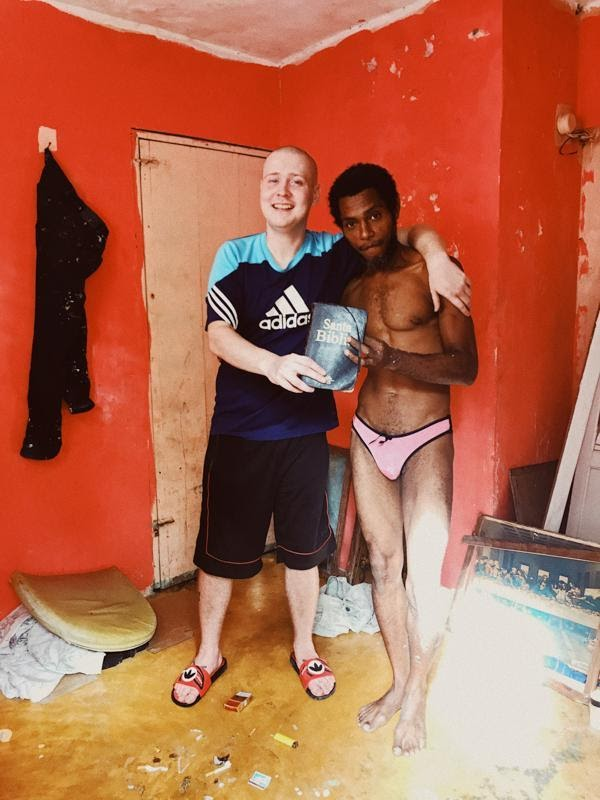 Two men embrace holding a bible in a red room in the Dominican Republic favelas during COVID-19