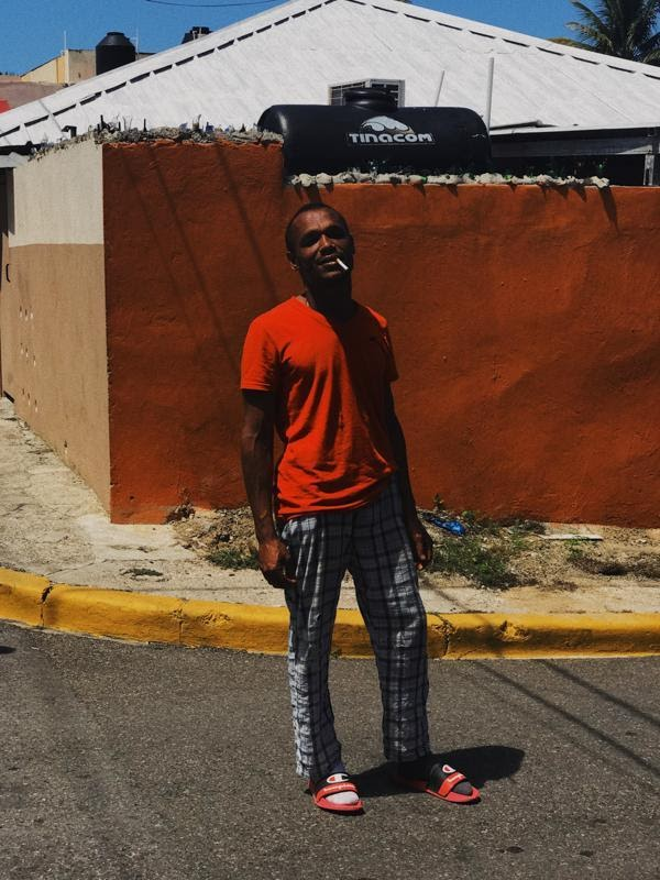A man wearing a red shirt and checkered trousers, with a cigarette in his mouth, in front of a red wall in the Dominican Republic, during COVID-19