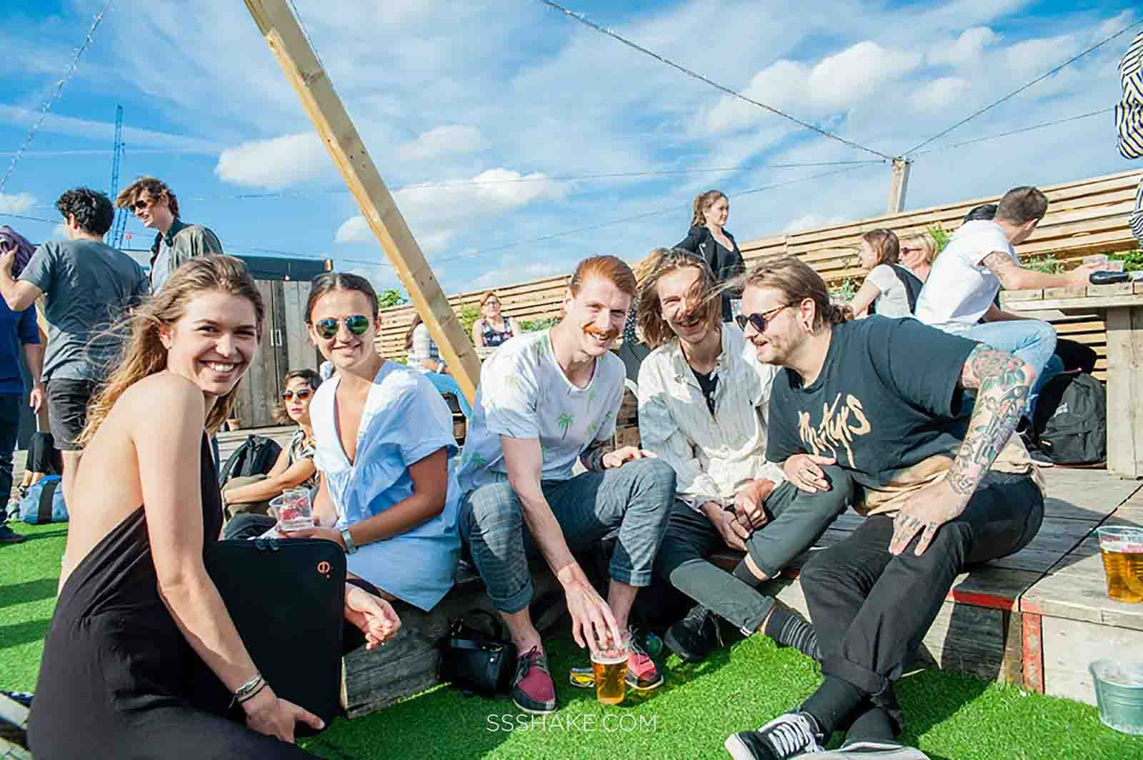 A group a people smiling and sitting in a circle on a rooftop with fake grass flooring and blue skies, at Netil 360, London, UK.