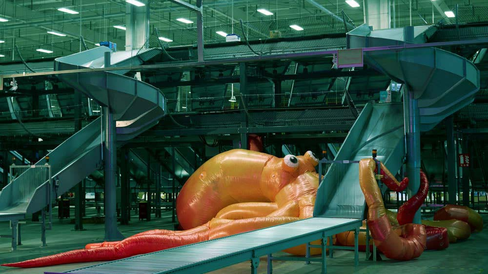 An installation of a huge orange blow-up octopus in a factory, by Cao Fei