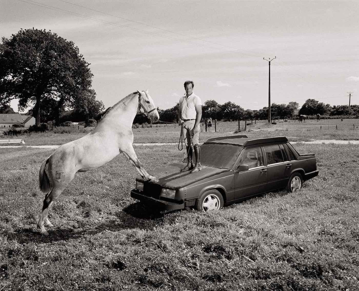 A man standing on top of a car in the middle of a field, holding a horse by its rein, in black and white