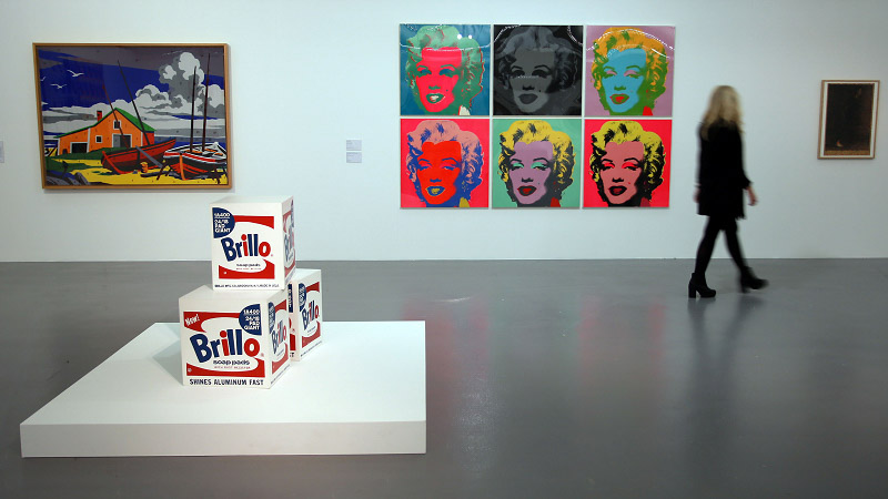 The interior of a gallery, with a selection of works by Andy Warhol, from portraits of Marilyn Monroe, to packaging for Brillo