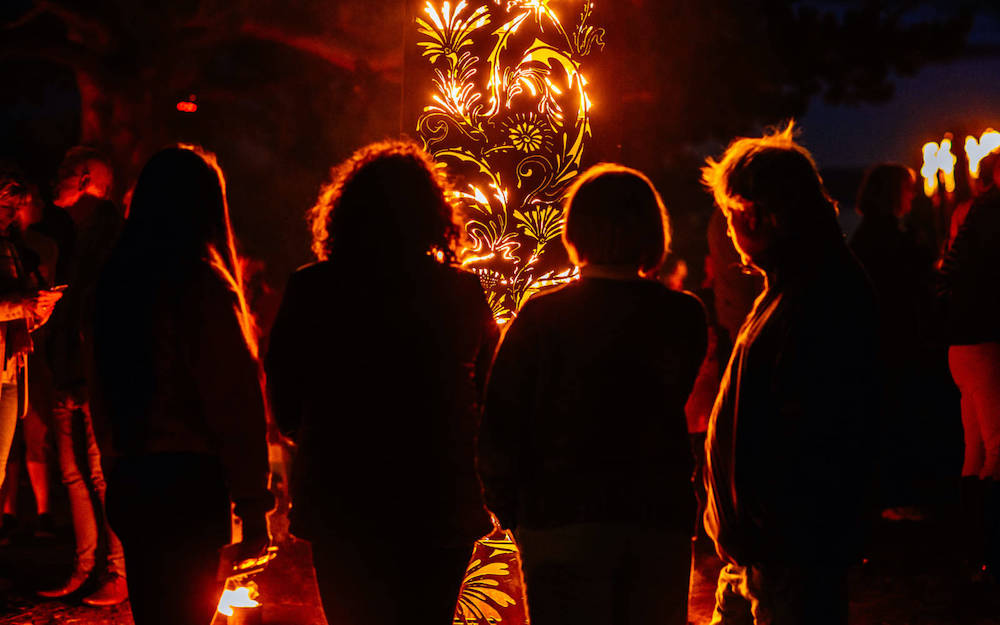 A group of people from behind, standing in front of a installation utilising fire