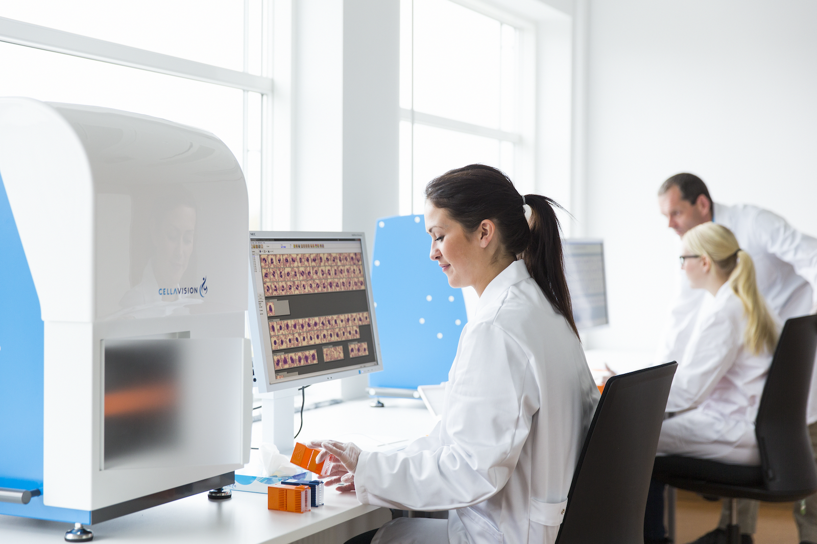 Female chemist sitting in front of a CellaVison blood analysis machine in a medical lab