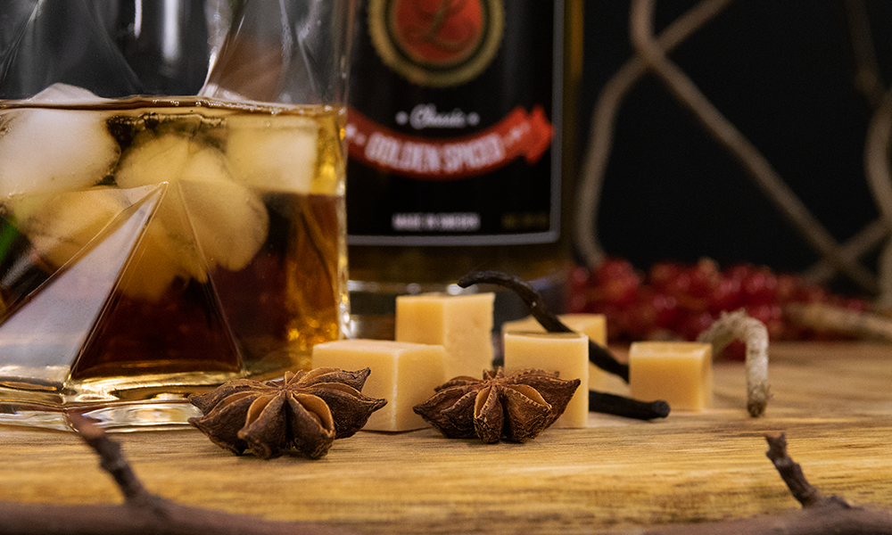 Fudge and vanilla on wooden table with glass of Rhum with Ice