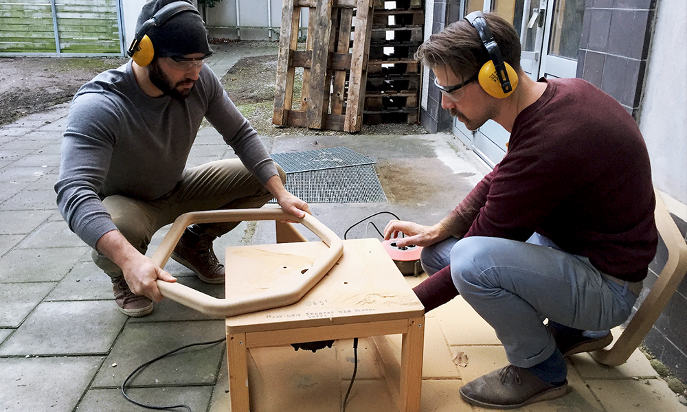 Two male designers wearing ear protectors working on a soil compactor prototype in wood materials