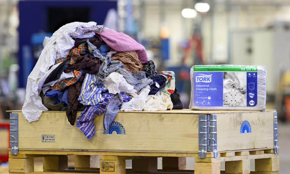 A pile of fabrics and a Tork Cleaning Cloth packaging laying on a wooden pallet