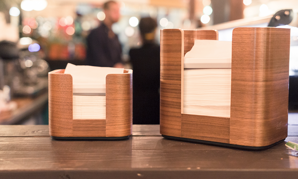 Two wooden Tork Xpressnap dispensers at a counter in a social environment