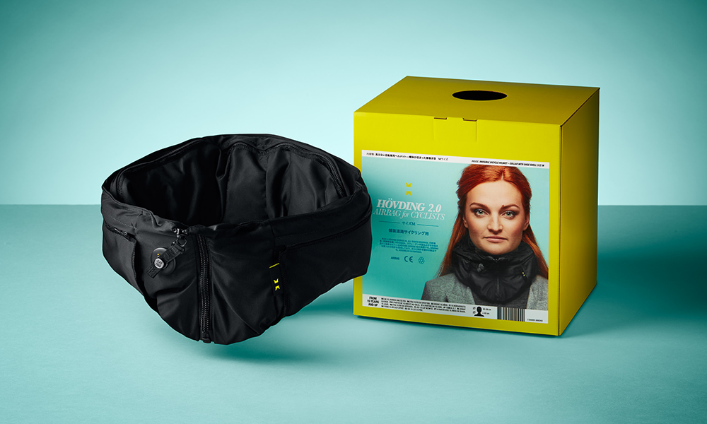 Hövding bicycle helmet and its yellow packaging photographed on turquoise background