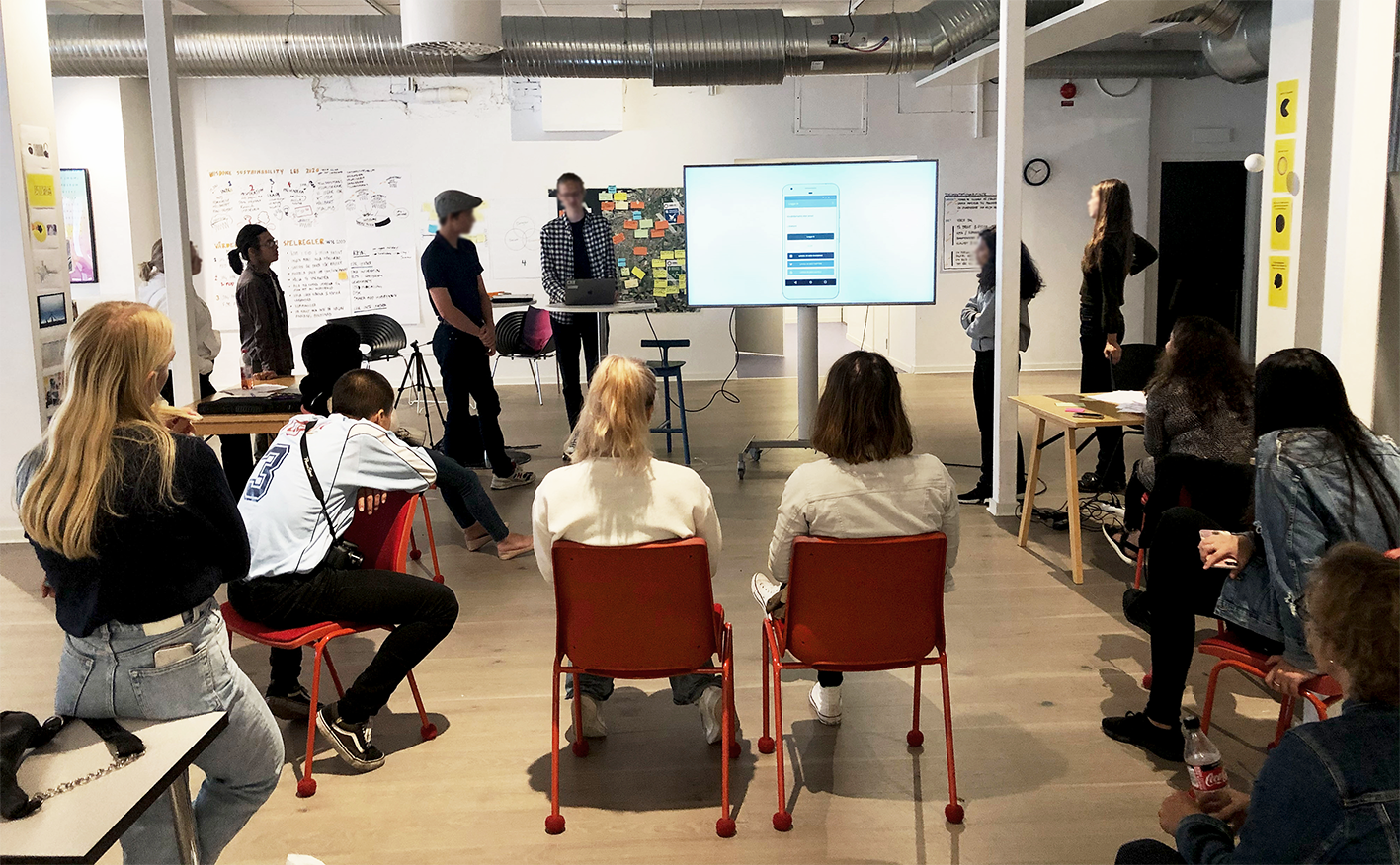 People sitting in a workspace and looking at a presentation