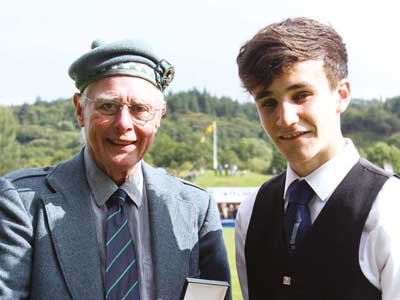 Andrew Ferguson, Dollar Academy, winner of the MacGregor Memorial receives the Silver Medal from Mr Ian Tegner