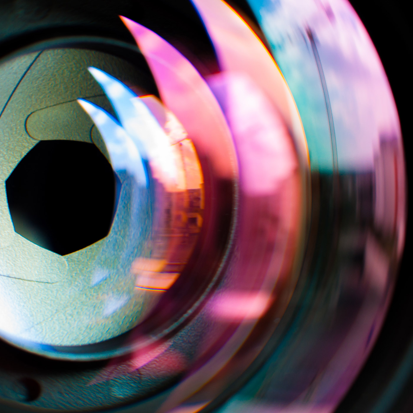 A close up of a camera shutter lens with rainbow reflection.
