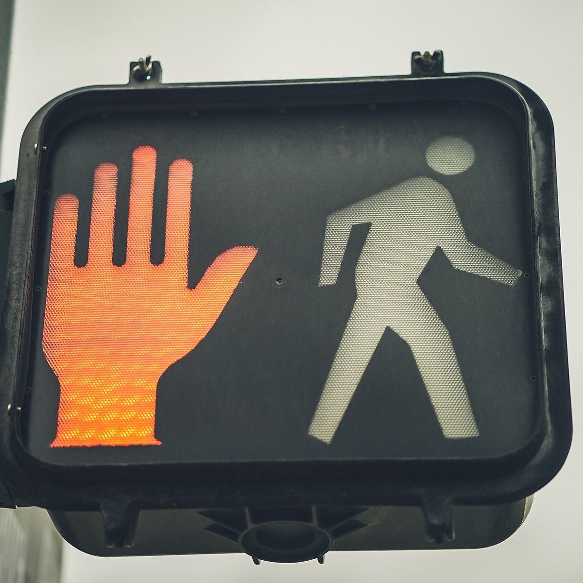 Stop walk traffic light sign with orange stop hand illuminated.