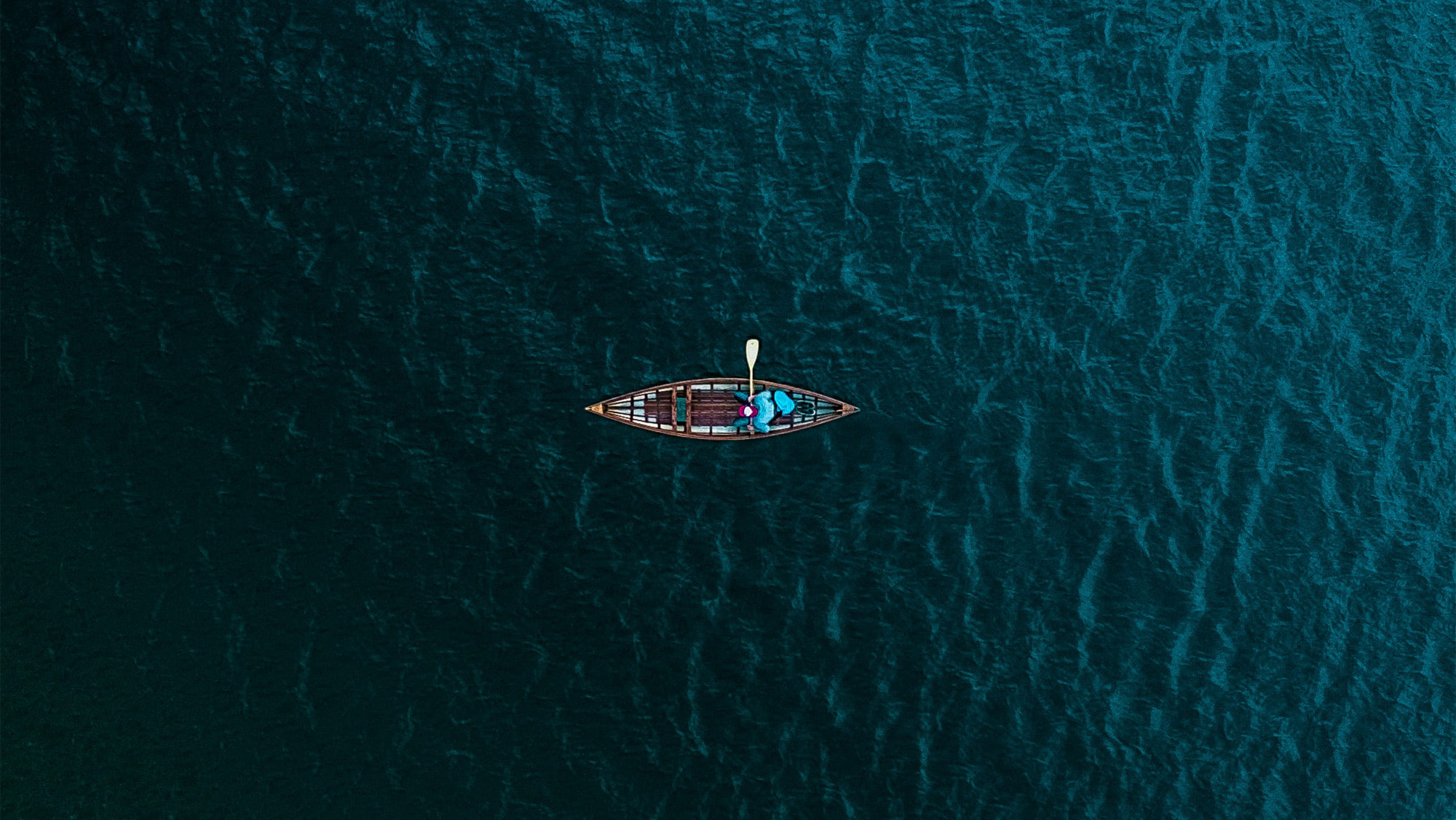 A man kayaking across the ocean.