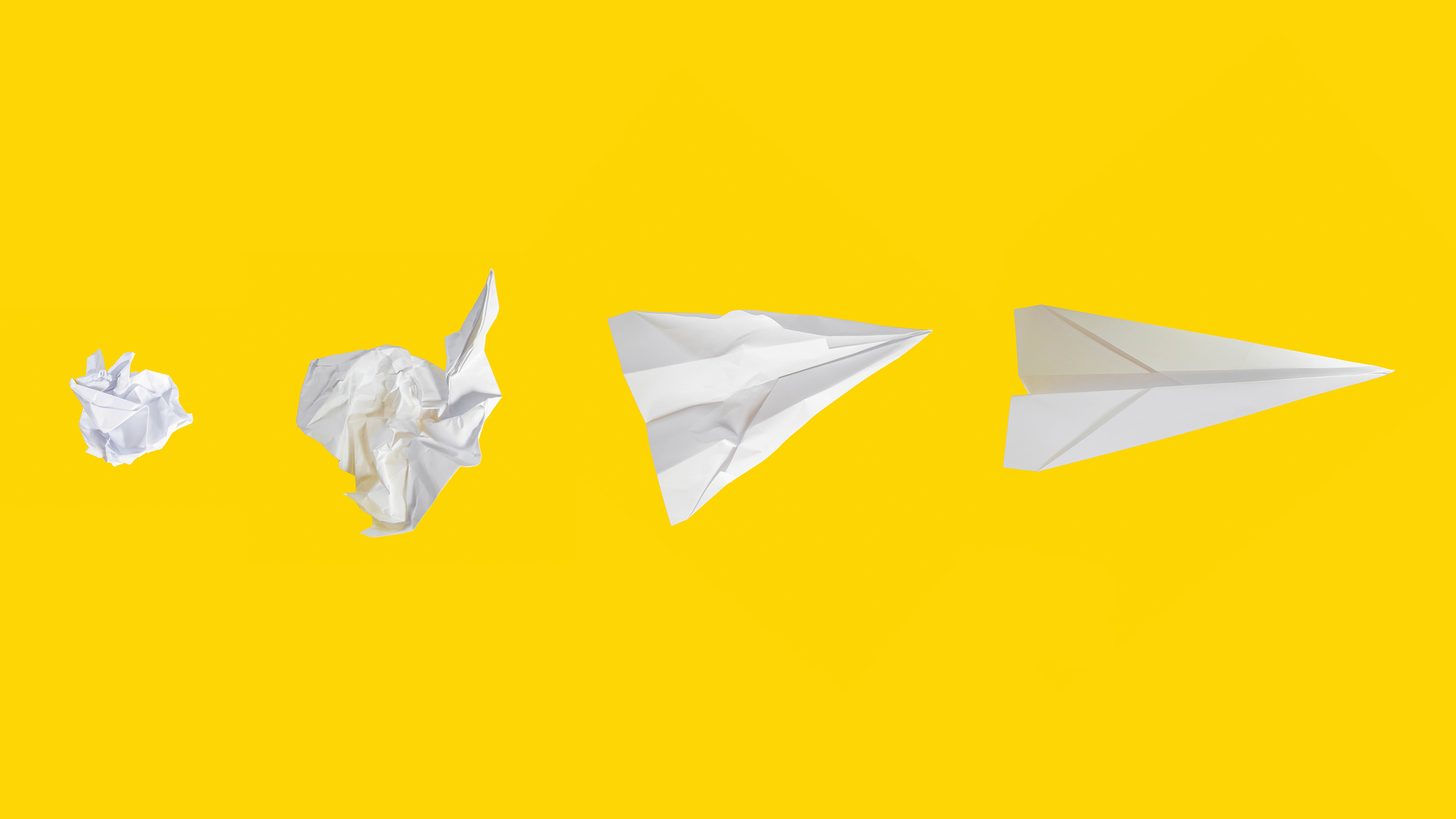 Crumpled paper aeroplanes on a yellow background.