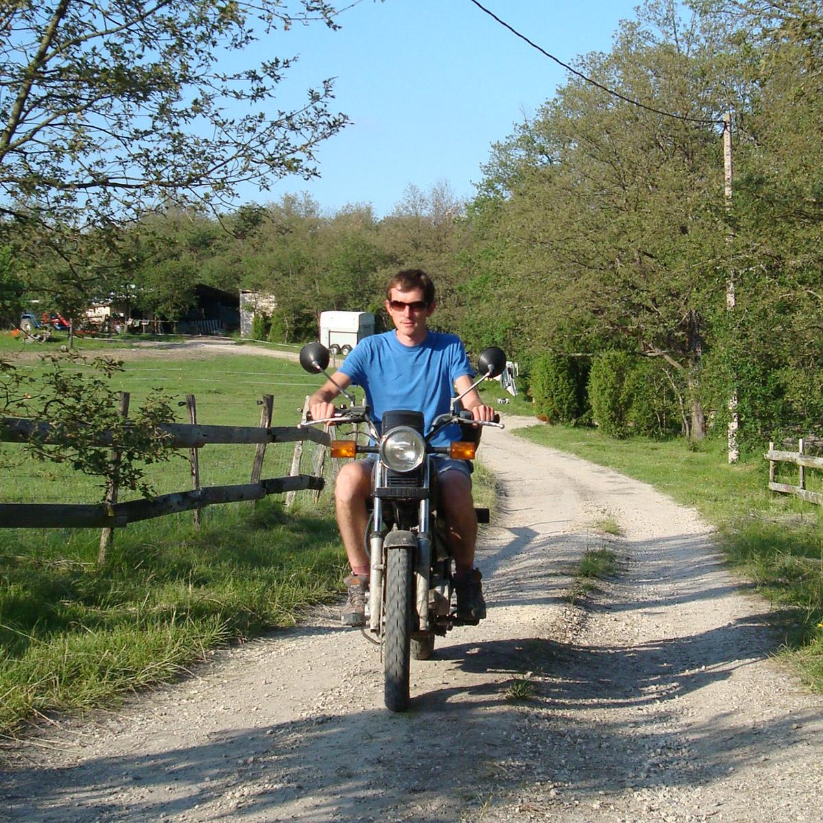 Man riding motorbike on dirt track.