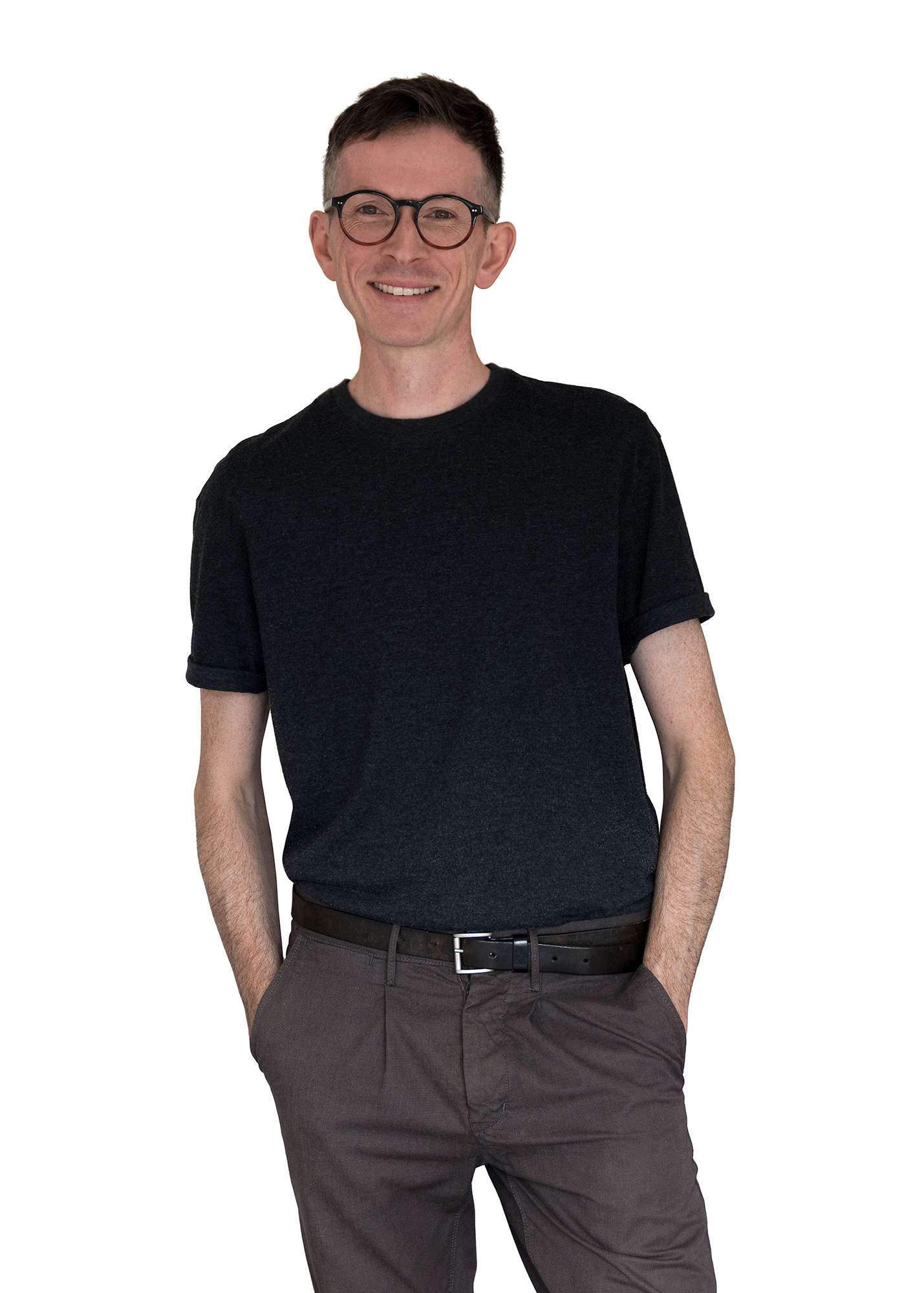 A man stood with his hands in pockets and smiling.