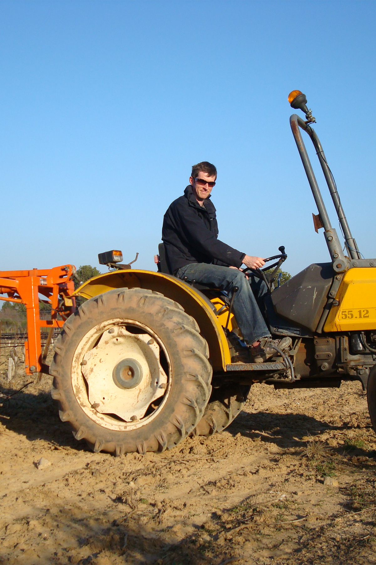 A man driving a yellow tractor through a bare field.